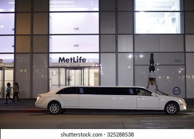 New York, New York, USA - May 11, 2012: A stretch limousine is parked on Sixth Avenue in midtown Manhattan in the early evening. The driver as well as people walking on the street can be seen.