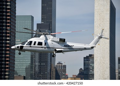 NEW YORK, USA - MAY 12, 2016: Helicopter takes off from 34th street Heliport. The United Nations building and other skyscrapers are in the background.