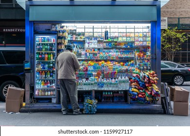 New York, USA - May 14, 2018: Man running a roadside kiosk selling snacks and drinks in New York City
