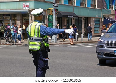 New York, USA - May 2, 2018: Policeman directs traffic at a crossroad