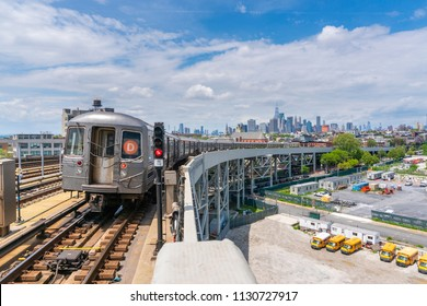 New York, USA - May 21, 2018: Subway train leaving a station in New York with skyline in the background. Subway in New York is the largest and also one of the oldest public transit systems.