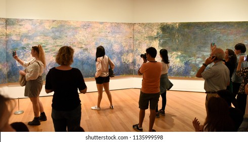 New York, USA - May 25, 2018: A visitors looks at the Claude Monet Water Lilies painting in Museum of Modern Art in New York City.
