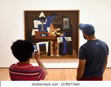 New York, USA - May 25, 2018: A visitors near the Pablo Picasso Three Musicians painting in Museum of Modern Art in New York City.