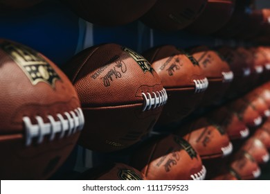 NEW YORK, USA - MAY 28, 2018: Rows of american football balls in NFL Experience in Times Square, New York, a first-of-its-kind live action attraction, combining interactive games and 4D theatre.