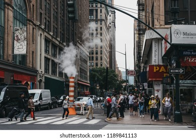 New York, USA - MAY 28, 2018: People crossing Fifth Avenue on a zebra crossing in New York, past the steam vapour orange and white stack. New York is one of the most visited cities in the world.