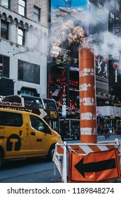 New York, USA - MAY 30, 2018: Yellow taxi drives past the steam vapour orange and white stack. Yellow taxis are recognised worldwide as the icons of the city.