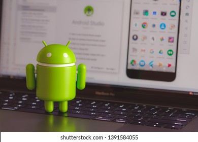 New York, USA - May 4, 2019 - Google Android figure standing on laptop keyboard with code in background