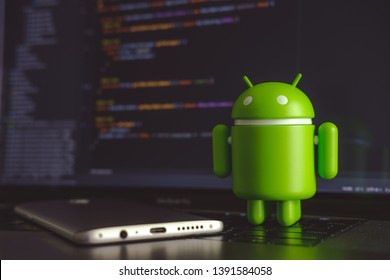 New York, USA - May 4, 2019 - Google Android figure standing on laptop keyboard next to mobile phone with code in background