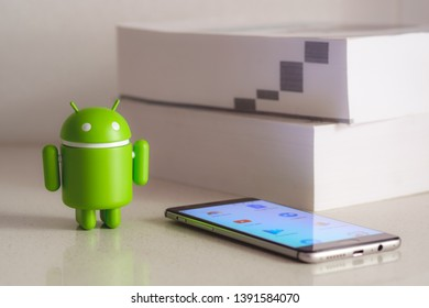 New York, USA - May 4, 2019 - Google Android figure standing next to mobile phone with books in the background