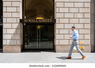 New York, USA - May 8, 2018: White collar worker walking pass a building at Wall Street. It is the world's most significant financial center.