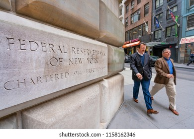 New York, USA - May 8, 2018: Man walking past the Federal Reserve Bank of New York. It is responsible for implementing monetary policy in the United States.