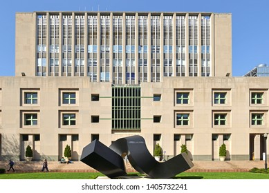 """NEW YORK, USA - MAY 8, 2019: Columbia University. Uris Hall, standing behind Clement Meadmore's 1968 sculpture """"Curl'"""