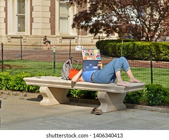 NEW YORK, USA - MAY 8, 2019: Columbia University. Female student preparing for exams on marble park bench