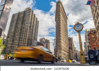 New York, USA - May 8th 2017:  Slow-shutter shot of a yellow new york taxi with the famous Flat Iron Building in the background, New York CIty, USA