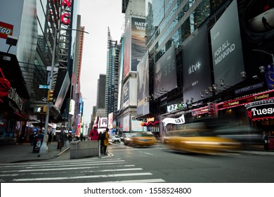 NEW YORK, USA - NOVEMBER 12, 2019: Traffic and pedestrians moving through the street under bright advertising billboards during rush hour on 7th Avenue in New York, USA.