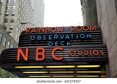 New York, USA - November 13, 2008: entrance marquee of nbc television studios building with billboards and grey skyscrapers on white sky background. Entertainment and tourist destination