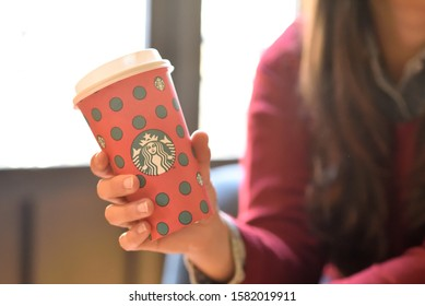 New York, USA - November 5, 2019 : Close up of a Woman drinking a tall Starbucks coffee in starbucks coffee shop with carrot cake. Starbucks is the world's largest coffee house with over 20,000 stores