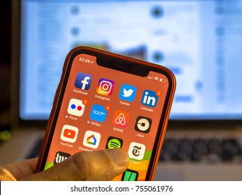 NEW YORK, USA - NOVEMBER 7, 2017: Social media app icons on new smartphone display close-up around other iphone applications with laptop in background