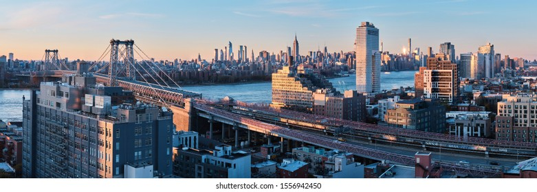 New York, USA - November 9, 2019 - Panorama of Williamsburg bridge in Brooklyn with Midtown Manhattan skyline in the background, New York City before sunset.