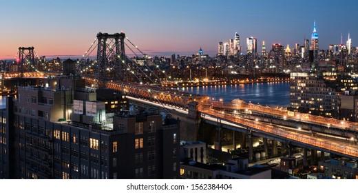 New York, USA - November 9, 2019 - Panorama of Williamsburg bridge in Brooklyn with Midtown Manhattan skyline in the background, New York City at night.