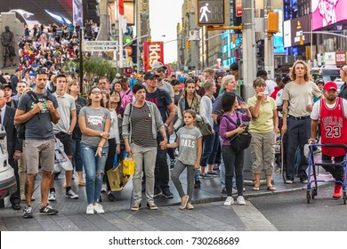 NEW YORK, USA  - OCT 4, 2017:  tourists and local people visit times square in late afternoon and wait at pedestrian crossing. Times square is a symbol for New York life and amusement.
