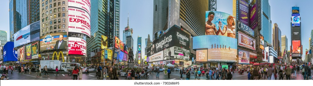NEW YORK, USA - OCT 4, 2017:  people visit times square with neon advertising of News, brands and theaters   in late afternoon. Times square is a symbol for New York life and amusement.