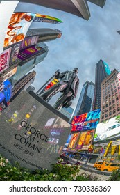 NEW YORK, USA - OCT 5, 2017:  neon advertising of News, brands and theaters at times square with statue of George m. Cohan in early morning. Times square is a symbol for New York life and amusement.