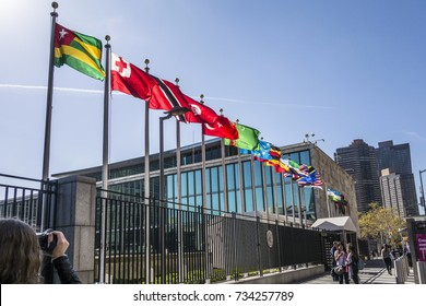 NEW YORK, USA - OCT 5, 2017:   UN Nations building with flags of participating countries in sun.