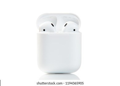 New York, USA - October 01, 2018: Apple airpods isolated on white background. Apple wireless earphones in charger box. Wireless headphones. Wireless technologies. Electronics.