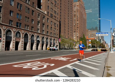 New York, USA - October 09, 2010: man with blue shirt and orange shorts and cap is running next to the bus lane in 1st Avenue on a bright sunny day with blue sky