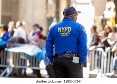 New York, USA - October 11, 2010: backside view of a police man from NYPD who looks relaxed to the crowd while columbus day parade