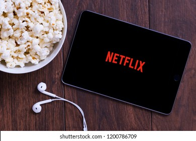 New York, USA - October 12, 2018: Table with popcorn bottle and Netflix logo on Apple Ipad mini and earphone. Netflix is a global provider of streaming movies and TV series.