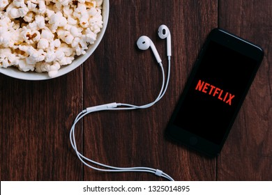 New York, USA - October 12, 2018: Table with popcorn bottle and Netflix logo on Apple Iphone and earphone. Netflix is a global provider of streaming movies and TV series.