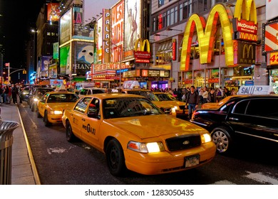 New York, USA - October 13, 2010: yellow taxis in front of McDonald's restaurant and several theatres at Times Square at night