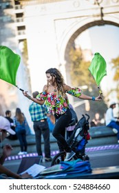 NEW YORK, USA - October 17, 2016. Woman Juggling with Flags while Riding Unicycle, in the Middle of Washington Square Park, Greenwich Park in New York City.