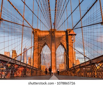 New York, USA, October 2016: early morning on a fast empty and orange glowing Brooklyn bridge right after sunrise