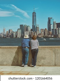 New York, USA, October 2018. Middle-aged couple, over fifty years old, with their backs, observing the New York skyline, with its skyscrapers, from the Isle of Liberty.