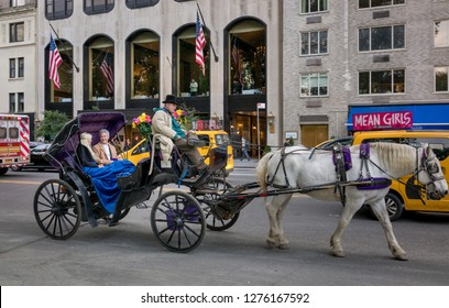 NEW YORK, USA - OCTOBER 22, 2018 : Unknown romantic couple at buggy carriage with coachman along Central Park in New York City, USA.