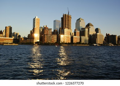 New York, USA - October 5, 2018: View of Riverside Park next to the city skyline at sunset from the Hudson River.