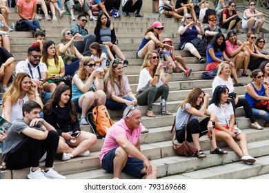 NEW YORK, USA - Sep 17, 2017: Manhattan street scene. New York and New Yorkers. A group of people watching the performances of artists sitting on the steps in the central park of New York