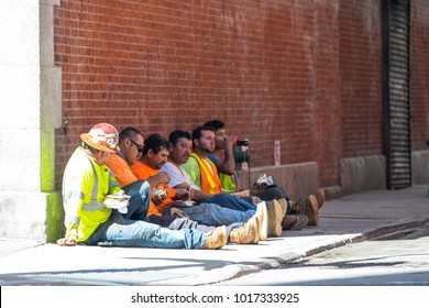 NEW YORK, USA - SEPTEMBER 10, 2017: View of the construction workers having lunch while sitting at the ground