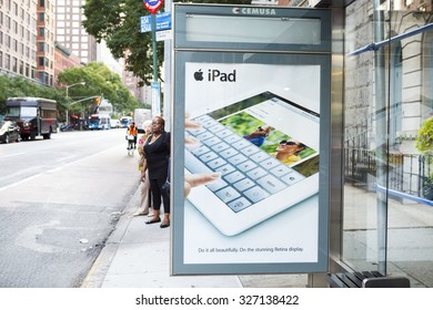 New York, New York, USA - September 13, 2012: An iPad poster on a bus stop on 34th Street in Midtown Manhattan. People can be  seen waiting for a bus as well as someone on a bicycle.