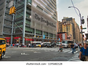 New York, USA, September 19, 2018. Traffic of vehicles and crowd of people walking, near the building of the New York Times, in the Eighth Avenue of Manhattan, at dusk.
