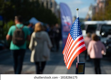New York, USA - September 19 2020: American flag waving on the car on the 4th of July, thanksgiving day or during United States Presidential election with people and cars on background