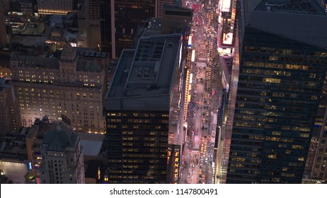NEW YORK USA - SEPTEMBER 23 2016: AERIAL HELI SHOT: Flying above crowded busy Seventh Avenue towards flashy Times Square entertainment center adorned with billboard ads and neon signs glowing at night