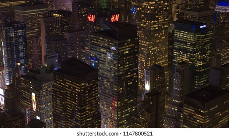 NEW YORK USA - SEPTEMBER 23 2016: Flying above the contemporary skyscrapers towards flashy Times Square amongst the buildings lit up at night. Flashing signs & billboards reflecting in glassy facade