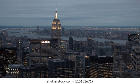 NEW YORK USA - SEPTEMBER 23 2016: AERIAL HELI SHOT, CLOSE UP: Flying above lit up skyscrapers and corporate buildings in Midtown Manhattan New York City looking towards Hudson River and New Jersey