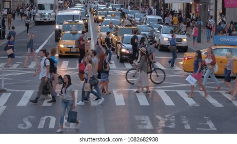 NEW YORK, USA - SEPTEMBER 23rd 2016: Local people and tourists walking on pedestrian crossing on crowded streets in New York. Yellow cabs and cars waiting on busy intersection in traffic jam at sunset
