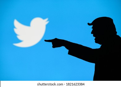 NEW YORK, USA, SEPTEMBER 25, 2020: Donald Trump versus Twitter. Silhouette of angry American President in conflict with Chinese social network Twitter. Logo of company on blue screen in background
