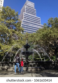 New York, USA - September 26, 2014:  Woman and child admire the view in lower Manhattan of City Hall park fountain